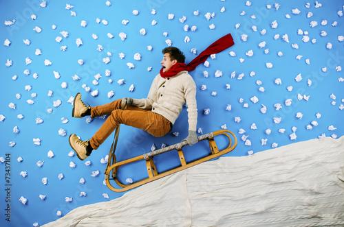Young man on sled having fun