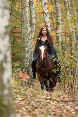 Amazing girl riding a horse without any equipment in autumn fore