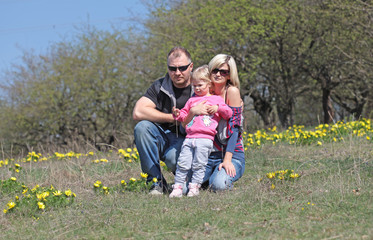 Happy mother, father and daughter in the park with yellow flower