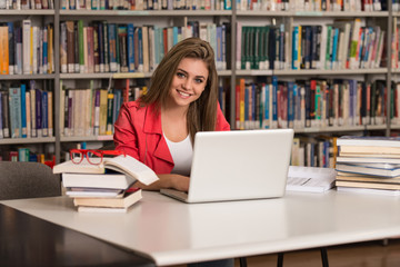 Happy Female Student Working With Laptop In Library