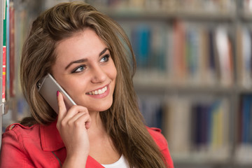 Female College Student Typing On Mobile Phone
