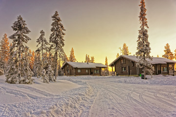 Two wooden cottages at winter Lapland