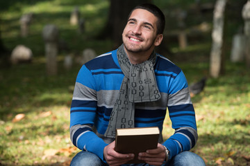 Handsome Young Man Reading A Book In The Park