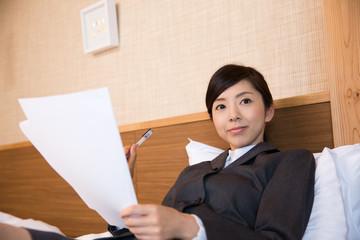 ベッドで書類に目を通すビジネスウーマン