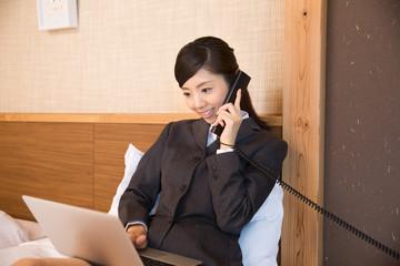 ベッドでPCを使用するビジネスウーマン