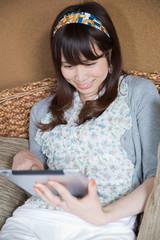 ソファでタブレットを操作する若い女性