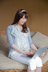 ソファでノートPCを操作する若い女性