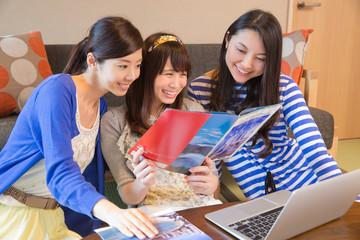 旅行の計画をする若い女性3人