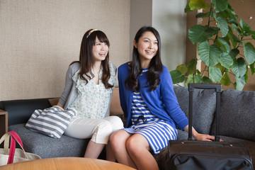 ホテルの客室でくつろぐ若い女性2人