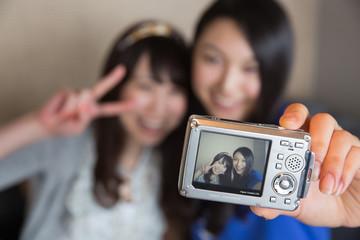 ホテルでデジカメで撮影する若い女性2人