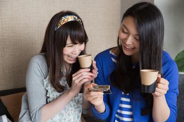 デジカメを一緒に見る若い女性2人