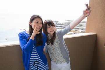 ホテルのベランダで撮影する若い女性2人