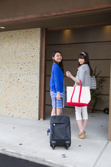 旅館の玄関から入っていく若い女性2人