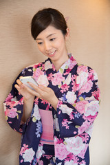 スマホを操作する浴衣姿の若い女性