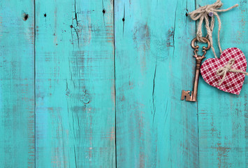 Bronze key and heart hanging on antique blue wood background