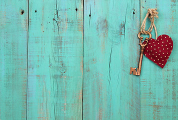 Bronze key and heart hanging on antique wooden background