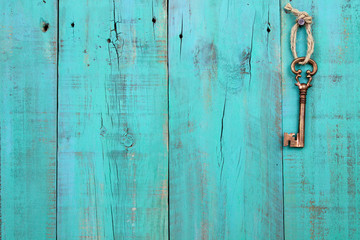 Bronze skeleton key hanging on antique blue wood background