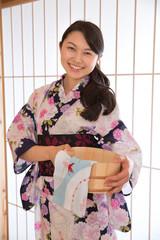 浴衣姿で桶と手拭いを持つ若い女性