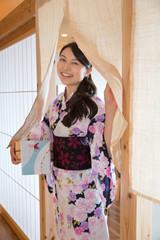 浴衣姿で暖簾をくぐる若い女性
