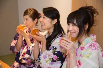 ビールを飲む浴衣姿の若い女性3人