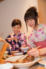 旅館の食事を食べる浴衣姿の若い女性2人