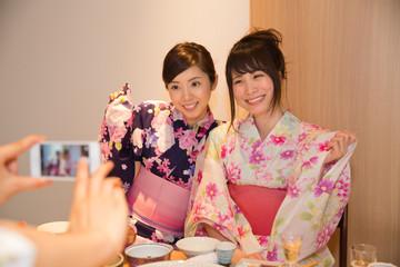 旅館の食事中にスマホで撮影する女性3人