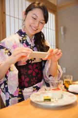 旅館の食事をスマホで撮影する浴衣姿の女性