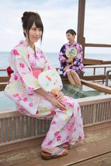 露天風呂の縁に座る浴衣姿の若い女性2人