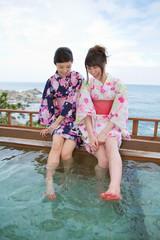 露天風呂で足湯を楽しむ浴衣姿の女性2人
