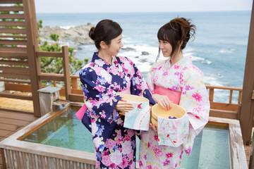 露天風呂の前に立つ浴衣姿の若い女性2人