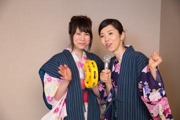 浴衣姿でカラオケを楽しむ若い女性2人