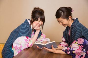 浴衣姿で旅館の中でくつろぐ若い女性2人