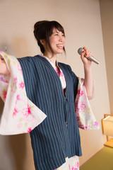 浴衣姿でカラオケを楽しむ若い女性