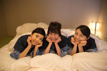 布団に寝そべりお喋りする若い女性3人