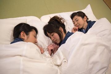 布団で寝る若い女性3人