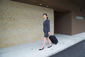 ホテルの玄関を歩くビジネスウーマン