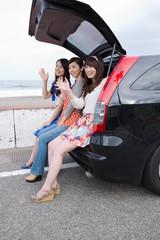 海岸で車にもたれかかる若い女性3人