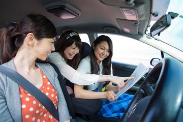 車の中で相談する若い女性3人