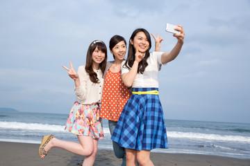 砂浜でスマホで撮影をする若い女性3人