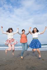 砂浜を手を繋いでジャンプする若い女性3人