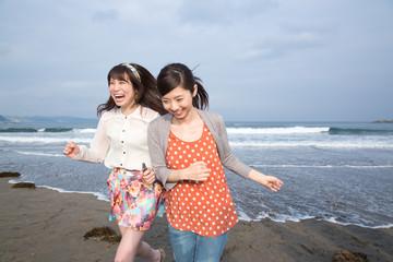 砂浜で遊ぶ若い女性2人