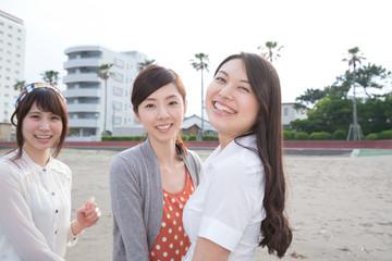 砂浜で遊ぶ若い女性3人