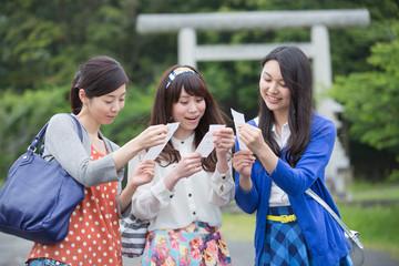鳥居の前でおみくじを読む若い女性3人