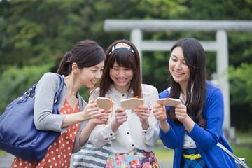 絵馬を見せ合う若い女性3人