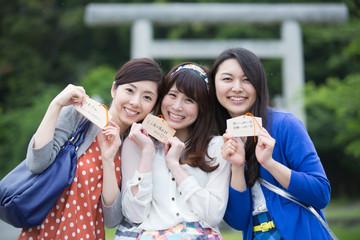 絵馬を見せる若い女性3人