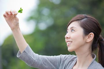 四つ葉のクローバーを持つ若い女性