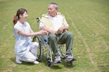 公園で休む車いすのシニア男性と介護福祉士