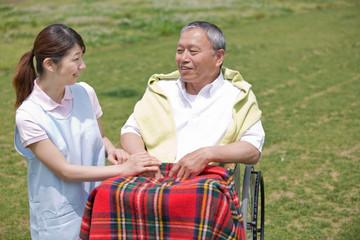 車いすに乗るシニアの手を握る介護福祉士