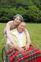 車いすに乗るシニア男性と肩を抱く女性