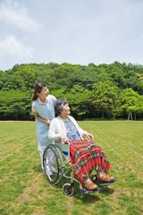 シニア女性の車いすを押す介護福祉士